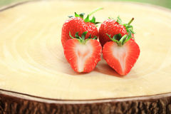 Fresh strawberry, sweet fruits, whole and cut in half, on the wooden chopping board. Royalty Free Stock Photography