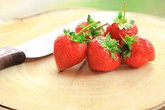 Fresh strawberry, sweet fruits, on the wooden chopping board with the knife. Stock Images