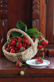 Fresh strawberry in a wattled basket. Still-life with a strawberry in a wattled basket and a strawberry berry in sugar stock photo