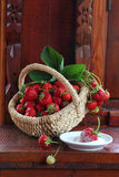 Fresh strawberry in a wattled basket. Still-life with a strawberry in a wattled basket and a strawberry berry in sugar stock photography