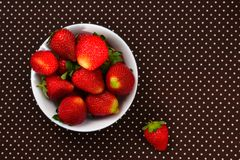 Fresh strawberry in a white plate on table. Top view Stock Photo