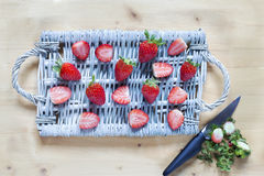 Fresh strawberry on a wicker tray and the rests with knife over Stock Images
