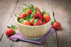 Fresh strawberry on wood plate, red tasty fruit on kitchen table Royalty Free Stock Images