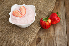 Fresh strawberry with yogurt in white bowl on wooden background. Stock Photos