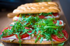 Fresh submarine baguette sandwich with ham, cheese, tomatoes and wild rocket. Selective focus.  royalty free stock images