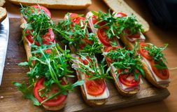 Fresh submarine baguette sandwich with ham, cheese, tomatoes and wild rocket. Selective focus royalty free stock image
