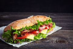 Fresh submarine sandwich. With ham, cheese, bacon, tomatoes, cucumbers, lettuce and onions on dark wooden background Stock Photos