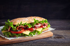 Fresh submarine sandwich. With ham, cheese, bacon, tomatoes, cucumbers, lettuce and onions on wooden cutting board stock photo