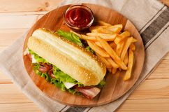 Fresh submarine sandwich with ham, cheese, bacon, tomatoes and Stock Images