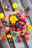 Fresh summer berries in a bucket. Fresh cherry, strawberry, blueberry and raspberry in a bucket on wooden table Stock Photo