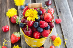 Fresh summer berries in a bucket. Fresh cherry, strawberry, blueberry and raspberry in a bucket on wooden table Royalty Free Stock Image