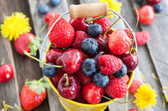 Fresh summer berries in a bucket. Fresh cherry, strawberry, blueberry and raspberry in a bucket on wooden table Stock Photos