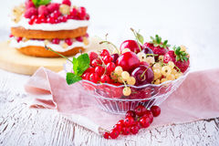 Fresh summer berries and fruits in glass bowl. On wooden rustic table, selective focus Royalty Free Stock Image