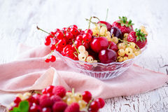 Fresh summer berries and fruits in glass bowl. On wooden rustic table, selective focus Stock Images