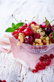 Fresh summer berries and fruits in glass bowl. On wooden rustic table, selective focus Royalty Free Stock Photography