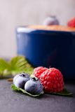 Fresh summer berries on slate stone with creamy dessert. Vertical photo of few summer berries as red raspberries and big blueberries on green leaves in front of Stock Photography