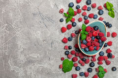 Fresh summer berries in vintage bowl. Over gray background,top view Stock Photos