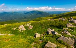 Fresh summer forenoon scenery in mountains. Beautiful with boulders on the grassy hill under the blue sky with some clouds royalty free stock photo