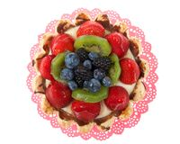 Fresh fruit tart on a pink doily isolated on white royalty free stock images