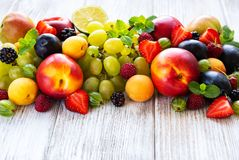 Fresh summer fruits and berries. On a white wooden table stock image