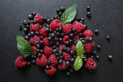 Fresh summer fruits on black background. Fresh summer fruits- raspberries and blueberries with mint leaf on black background Stock Images
