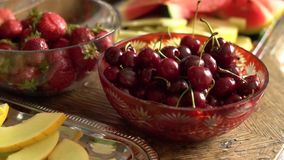 Fresh summer fruits: cherries, organic strawberries, melon slices, water melon in vintage crystal bowl on old wooden table.  stock video footage