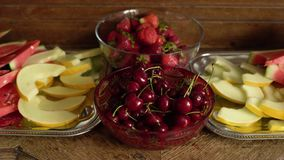 Fresh summer fruits: cherries, organic strawberries, melon slices, water melon in vintage crystal bowl on old wooden table.  stock video
