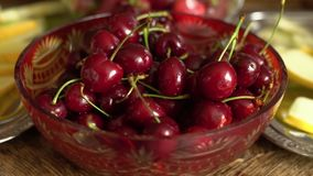 Fresh summer fruits - cherries in vintage crystal bowl on old wooden table.  stock video footage