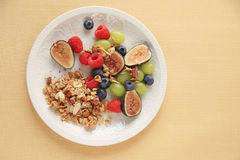 Fresh summer fruits with granola. Plate of granola with figs, raspberries, blueberries and grapes, copy space included Royalty Free Stock Photos