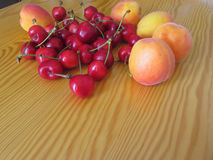 Fresh summer fruits on light wooden table . Apricots and cherries on wooden background.  Royalty Free Stock Images
