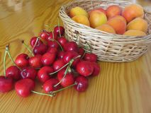 Fresh summer fruits on light wooden table . Apricots in a wicker basket and cherries on wooden background.  Royalty Free Stock Photos
