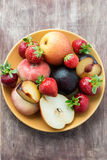 Fresh summer fruits in plate. Over wooden background Royalty Free Stock Photography