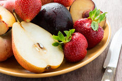 Fresh summer fruits in plate. Over wooden background with knife, closeup, selective focus Royalty Free Stock Images