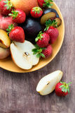 Fresh summer fruits in plate. Over wooden background, selective focus Stock Photos