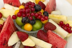 Fruits on a plate. Green plum, red currant, blueberry, strawberry, physalis, pitahaya, watermelon, orange and apple. stock photography