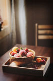 Fresh summer fruits on wooden plate. Strawberries, peaches and apricots. In rustic farm kitchen Royalty Free Stock Images