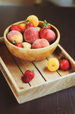 Fresh summer fruits on wooden plate. Strawberries, peaches and apricots. In rustic farm kitchen Stock Photos