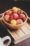 Fresh summer fruits on wooden plate. Strawberries, peaches and apricots. In rustic farm kitchen Royalty Free Stock Photo