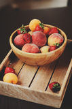 Fresh summer fruits on wooden plate. Strawberries, peaches and apricots. In rustic farm kitchen Royalty Free Stock Image