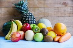 Fresh summer fruits on wooden table background - mix of fruits stock photography