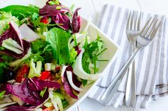 Fresh summer green salad mix on a wooden table. Fresh summer green salad mix with salad lettuce, spinach, fennel, celery, tomatoes, radish, olives, chicory and Royalty Free Stock Photography