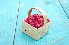 Fresh summer raspberry fruit  in wooden small basket. On old garden table Royalty Free Stock Photography