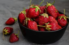 Fresh summer ripe strawberries in a black plate on a gray concrete background. Lit by the bright sun. Gray background. Flat lay. View from above royalty free stock photo