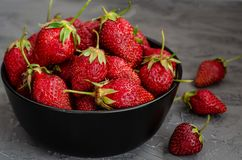 Fresh summer ripe strawberries in a black plate on a gray concrete background. Lit by the bright sun. Gray background. Flat lay. View from above stock images