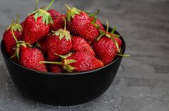 Fresh summer ripe strawberries in a black plate on a gray concrete background. Lit by the bright sun. Gray background. Flat lay. View from above royalty free stock image