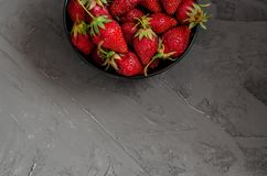 Fresh summer ripe strawberries in a black plate on a gray concrete background. Lit by the bright sun. Gray background. Flat lay. View from above stock photo
