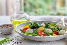 Fresh summer salad with arugula, yellow and red cherry tomatoes, Kalamata olives and mozzarella. Selective focus royalty free stock image