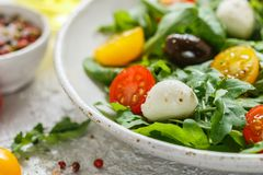 Fresh summer salad with arugula, yellow and red cherry tomatoes, Kalamata olives and mozzarella. Selective focus royalty free stock photography