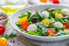 Fresh summer salad with arugula, yellow and red cherry tomatoes, Kalamata olives and mozzarella. Selective focus stock photos
