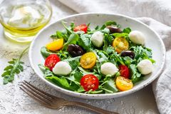 Fresh summer salad with arugula, yellow and red cherry tomatoes, Kalamata olives and mozzarella. Selective focus royalty free stock photos